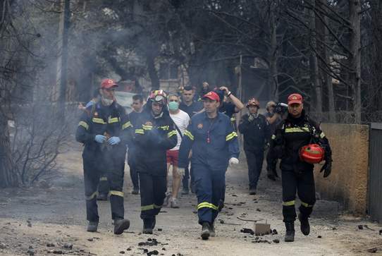 Firefighters work in Mati, east of Athens