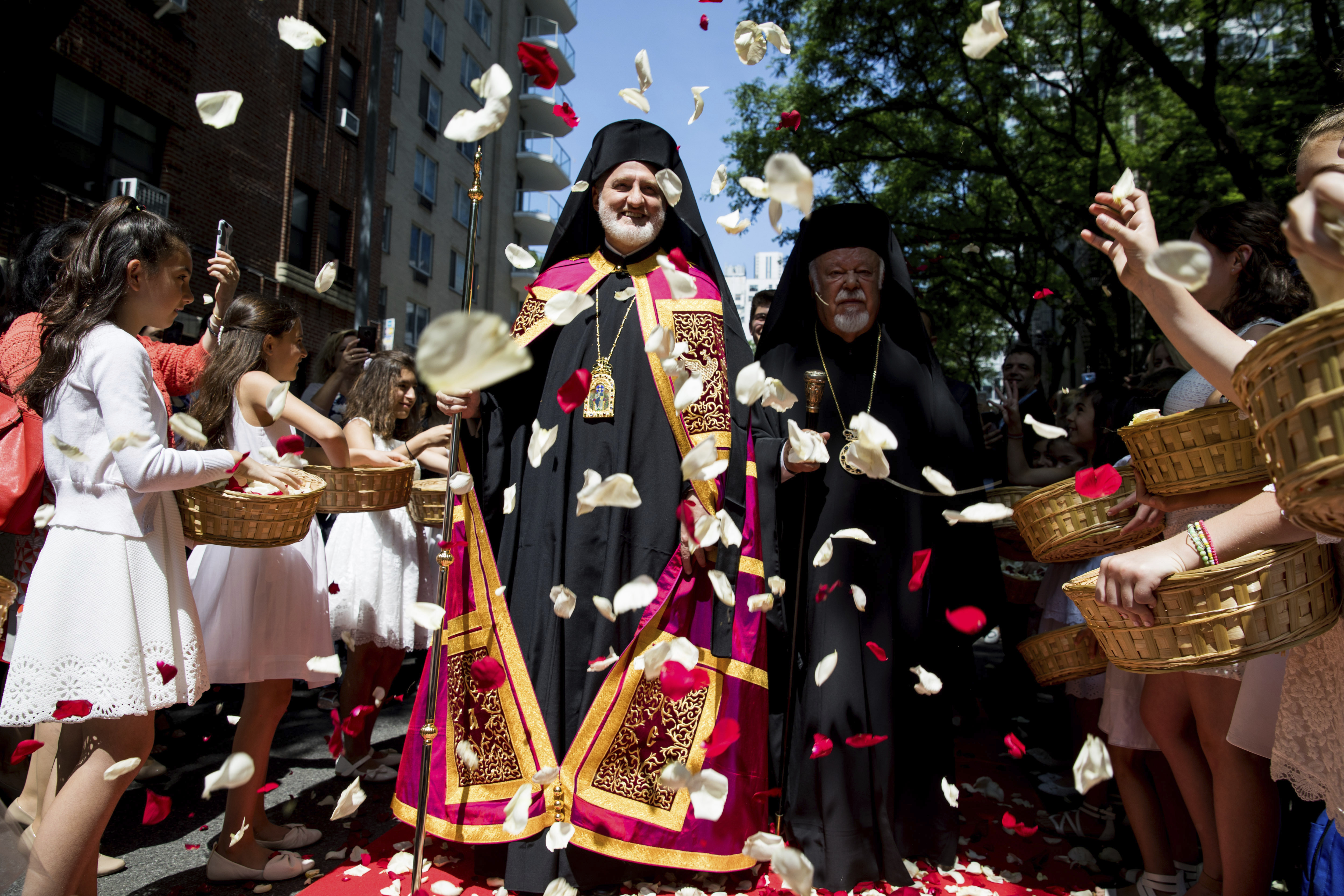 Archbishop Elpidophoros, center left, and Metropolitan Augoustinos of Germany, center right, walk toward the Archdiocesan Cathedral of the Holy Trinity for Elpidophoros' enthronement ceremony as the new archbishop for America as young girls throw flower petals, Saturday June 22, 2019, in New York. (AP Photo/Julius Motal)