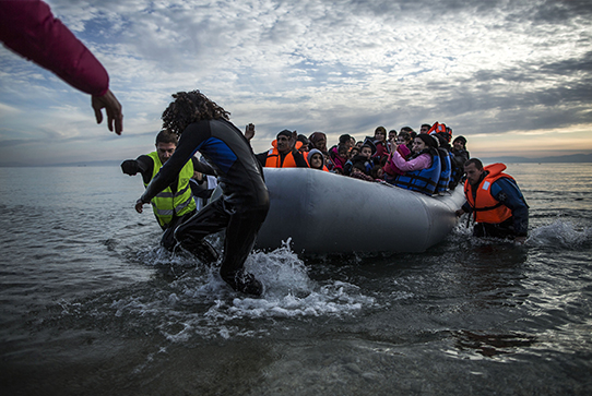 Migrants are helped by volunteers upon arrival on a dinghy to the Greek island of Lesbos